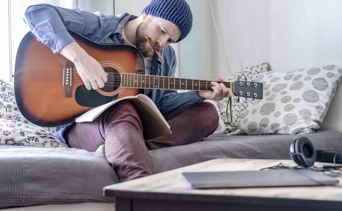 Focused composer plays written music on an acoustic guitar while